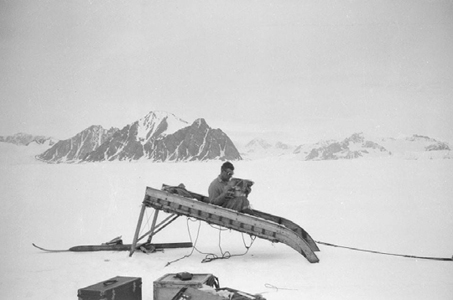 W.E.Hampton reading 'The Motor' on an upturned hard runner sledge, Neny Fjord