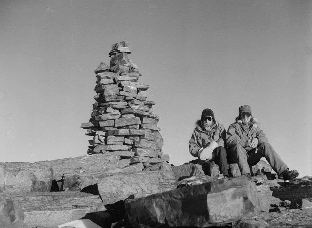 SPRI P55/15/44/3b. Alan Reece (assistant geologist) and Fred Roots (chief geologist) sit on a rock by a stone cairn.
